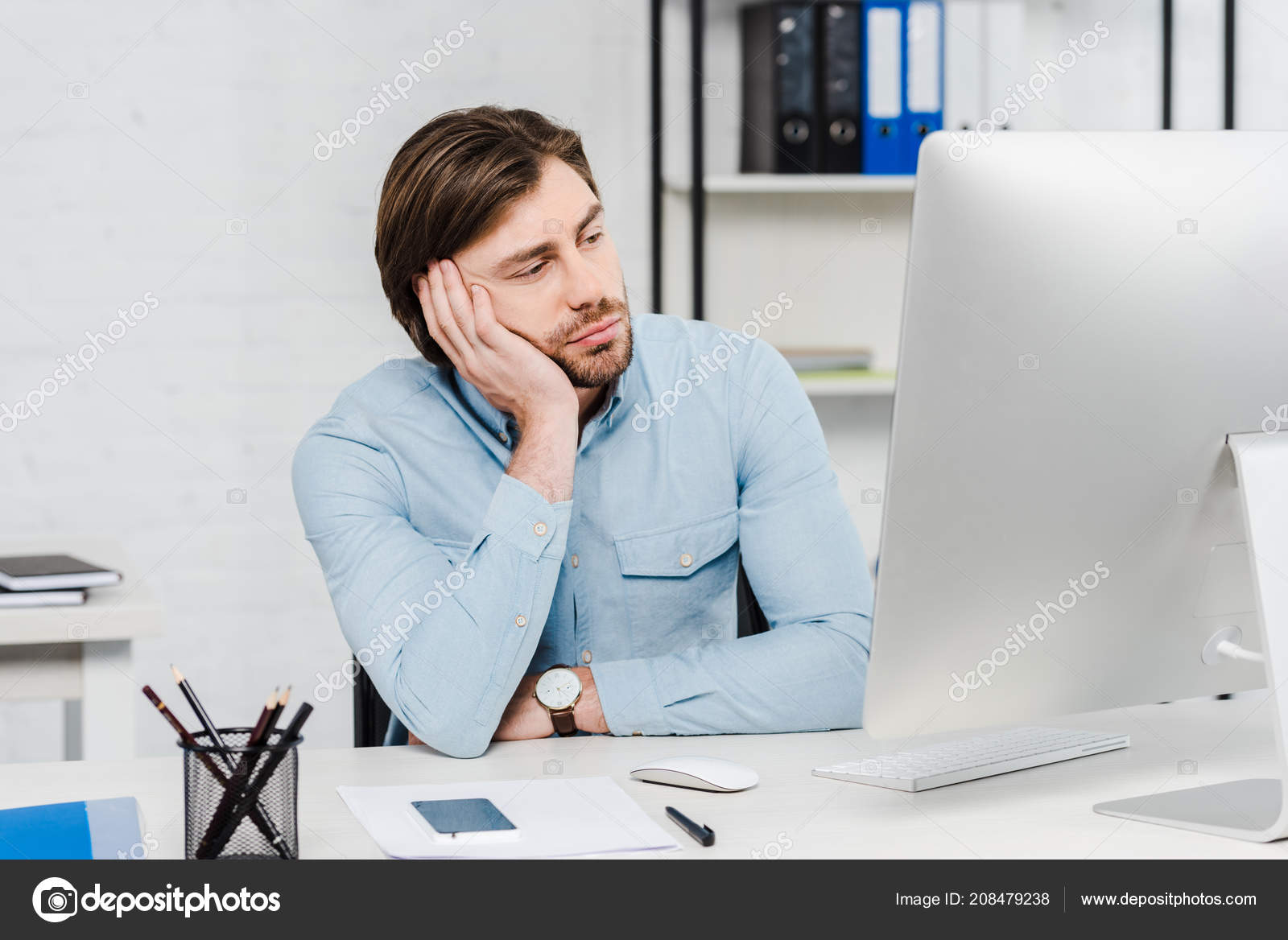 bored young businessman looking computer monitor modern office