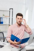 Fotografie handsome young businessman with folder and eyeglasses leaning back at workplace and looking at camera