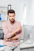 Photo handsome young businessman leaning back at workplace and looking at camera