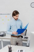 handsome young businessman reading documents in folder at modern office