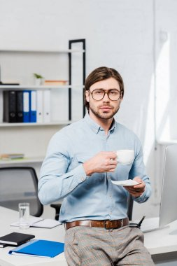 Handsome young businessman with cup of coffee looking at camera at modern office stock vector