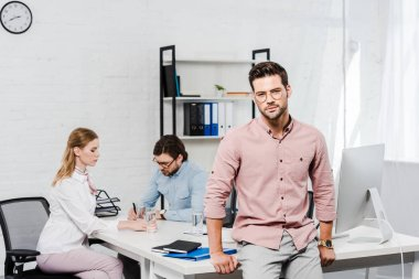 handsome young businessman looking at camera and leaning back on table at modern office while colleagues working together on background