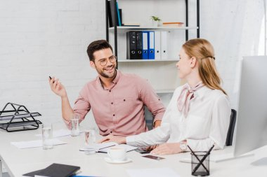 happy business people chatting at workplace in modern office