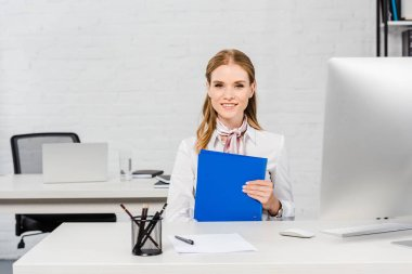 Happy young businesswoman with folder looking at camera while sitting at workplace stock vector