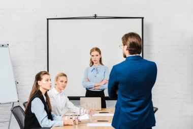 Rear view of boss talking to managers during meeting at modern office stock vector