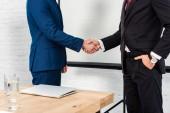 Fotografie oříznuté shot podnikatelů potřesení rukou v moderní kanceláři