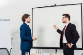 businessmen having conversation and pointing at presentation board at modern office