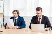 sikeres üzletemberek, dolgozó iratok és laptop együtt modern irodában