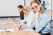 Fotografie confident young businesswomen sitting at conference hall and writing documents