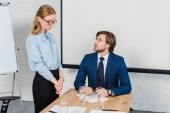 young boss talking to sad female manager at modern office