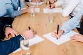 Fotografie oříznutý snímek týmu podnikatelů psaní na prázdné papíry na kongresový sál