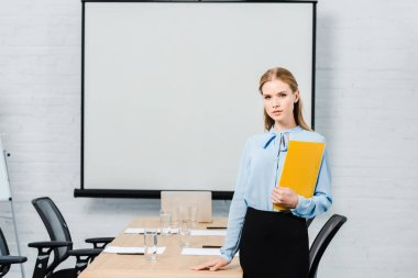 Confident young businesswoman with folder looking at camera in conference hall with blank presentation board stock vector