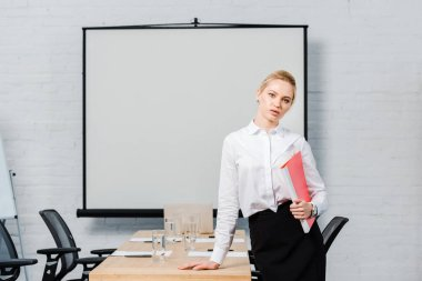 Attractive young businesswoman with folder looking at camera in conference hall with blank presentation board stock vector