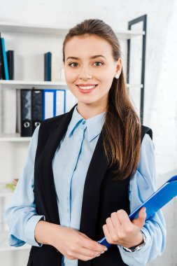 happy young businesswoman with folder of documents looking at camera at modern office