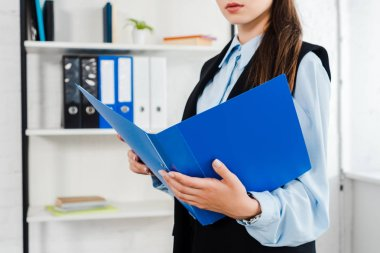 Cropped shot of young businesswoman with folder of documents at modern office stock vector