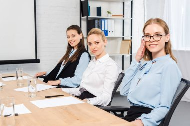 confident young businesswomen sitting at conference hall and looking at camera