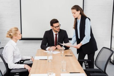 young businesswomen showing documents to their boss at modern office