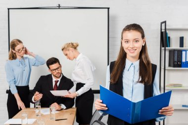 smiling young businesswoman with documents standing at modern office with colleagues having conversation on background