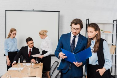 business people discussing documents together at modern office