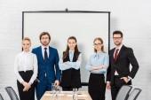 Fotografia squadra di gente di affari in piedi presso la sala conferenze e rivolto verso lobiettivo