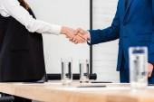 Fotografie oříznuté záběr potřesení rukou v moderní kanceláři se spolupracovníky