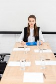 Fotografie beautiful young businesswoman sitting at table in conference hall at modern office