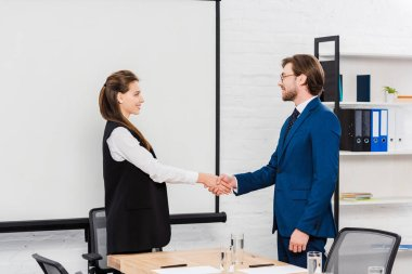 successful young business colleagues shaking hands during meeting