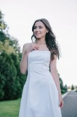 happy beautiful bride posing in traditional white wedding dress
