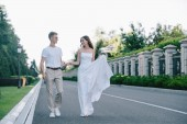 Fotografie attractive bride and handsome groom holding hands and walking on road
