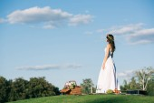 Fotografie attractive bride in wedding dress on romantic picnic with wicker basket on lawn