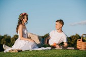 Fotografie beautiful wedding couple resting on picnic with fruits