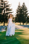 Fotografie beautiful happy young bride holding wedding bouquet and smiling at camera in park