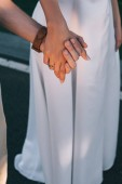 close-up partial view of romantic young wedding couple holding hands outdoors