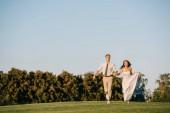 Fotografia felice giovani sposi in esecuzione sul prato verde nel parco