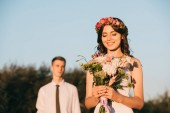 Fotografie beautiful happy young bride holding wedding bouquet and groom standing behind