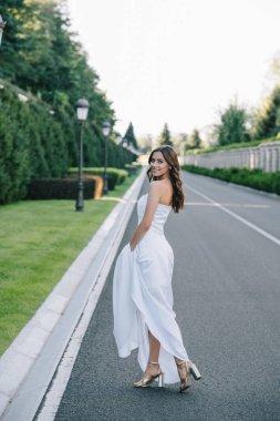 back view of happy bride in wedding dress walking on road