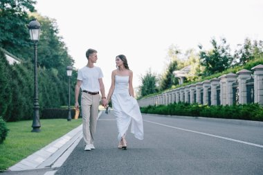 bride in wedding dress and groom holding hands and walking on road
