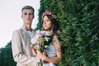 beautiful elegant wedding couple with floral bouquet