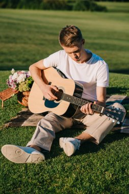young man playing acoustic guitar during picnic on green lawn