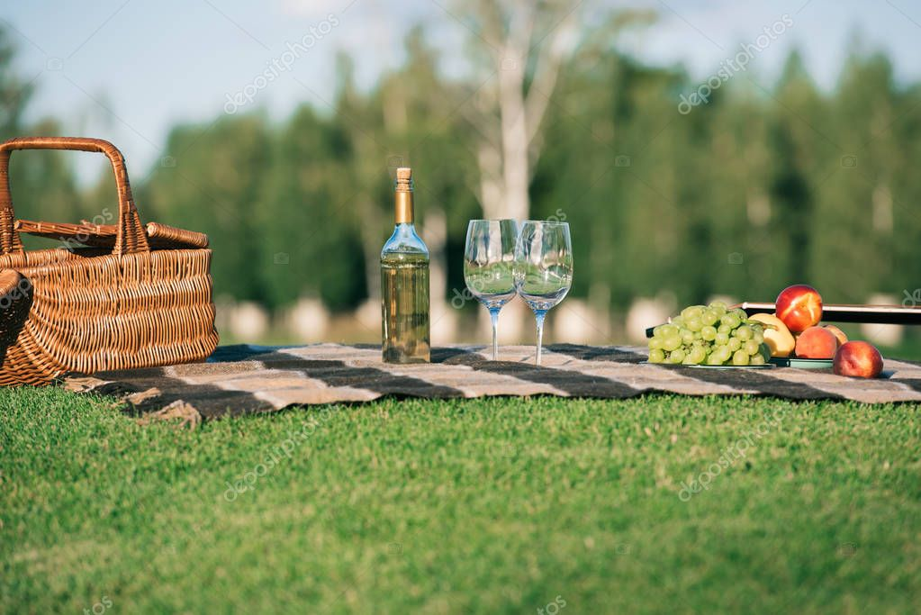 picnic with glasses, bottle of white wine, fruits and wicker basket on blanket on grass