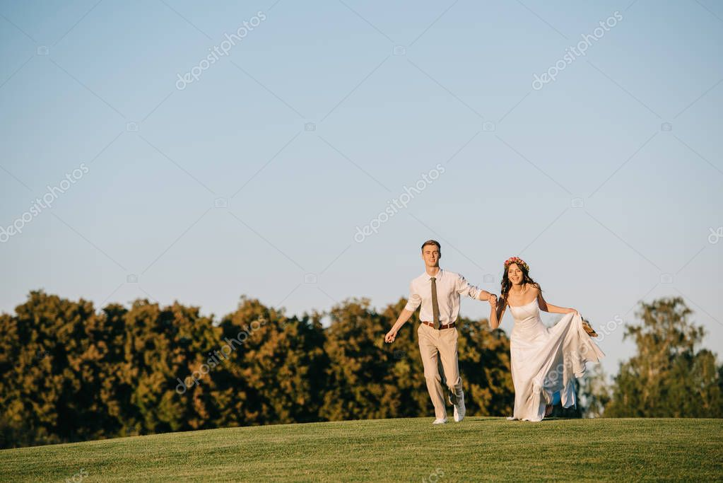 beautiful happy young wedding couple running on green meadow in park