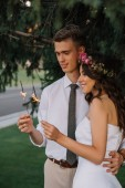 beautiful happy young wedding couple embracing and holding sparklers