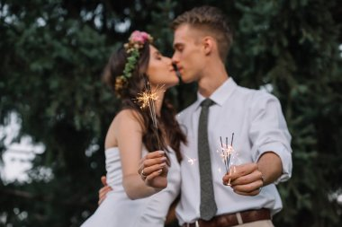 beautiful young wedding couple kissing and holding sparklers