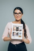 portrait of smiling brunette woman in eyeglasses showing tablet with pinterest website on screen in hands isolated on grey