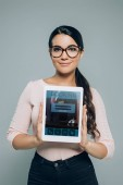Fotografie portrait of smiling brunette woman in eyeglasses showing tablet with booking website on screen in hands isolated on grey
