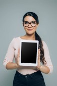 Photo woman showing digital tablet with blank screen, isolated on grey