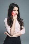 mladá žena trpí zuby s červený bolestivý bod, izolované Grey