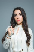 Fotografie portrait of attractive girl posing in white suit with necklace, isolated on grey