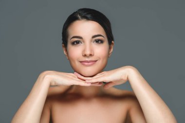 portrait of attractive brunette woman with bare shoulders looking at camera isolated on grey