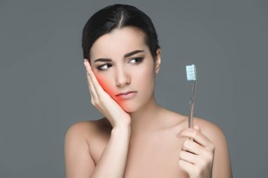 portrait of brunette woman with tooth brush having tooth ache isolated on grey